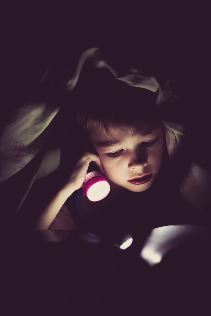 reading by flashlight after dark outside