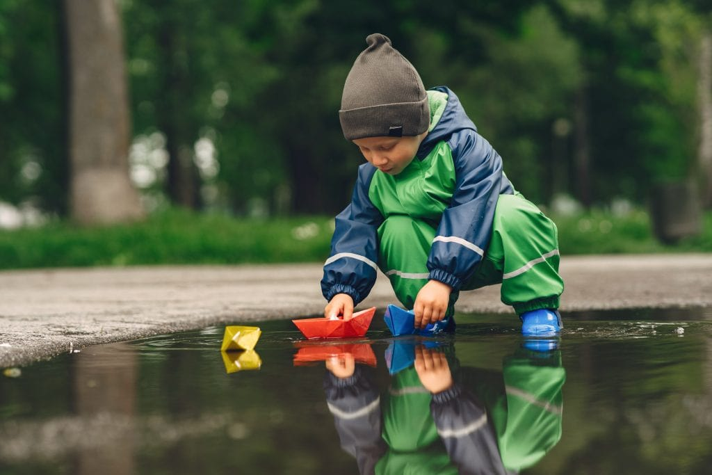 boy plays with handmade boats in puddle