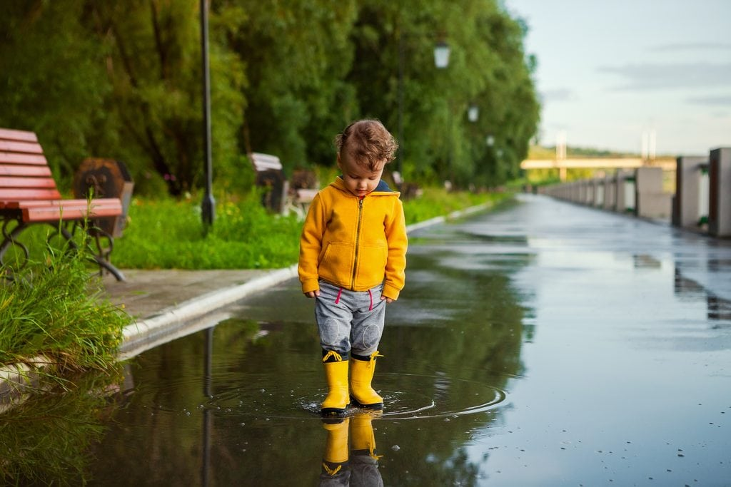 child playing in puddle after the rain