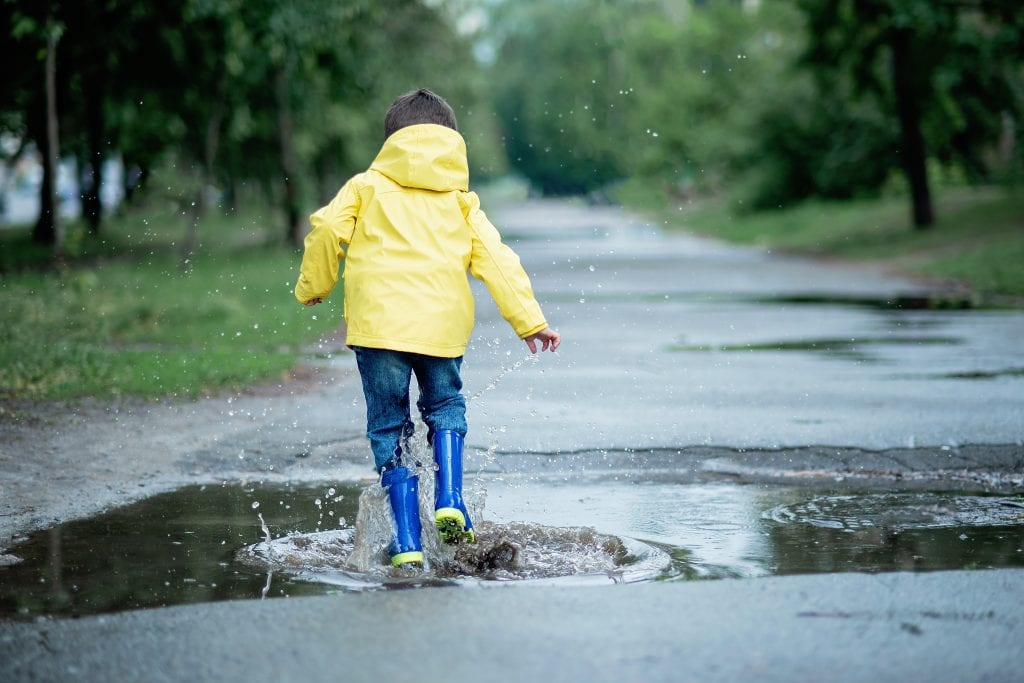 boy has fun jumping in puddles on rainy day