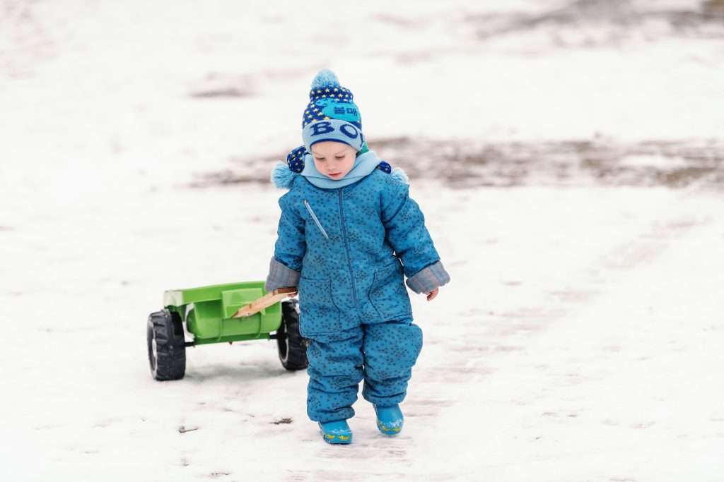 boy playing outside in snow on winter day