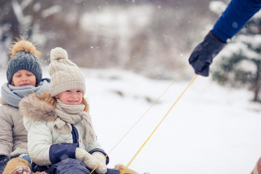 children sledding outside on snowy  winter day