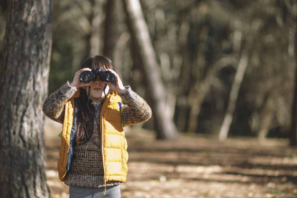 child using binoculars on a hike