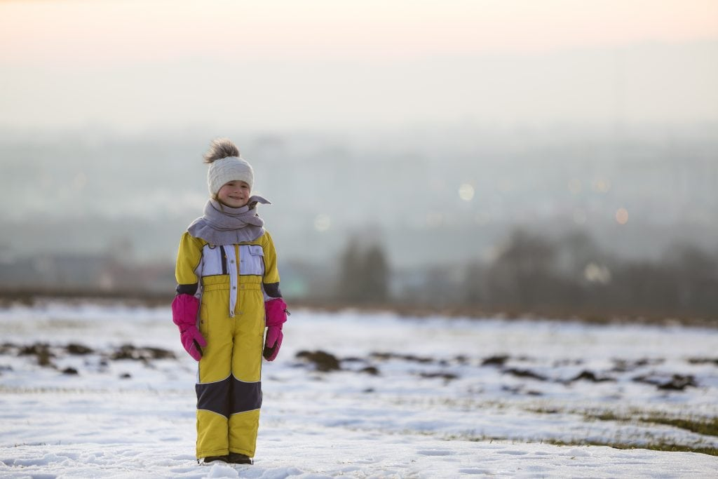 child standing outside in snow dressed in layers and warm accessories