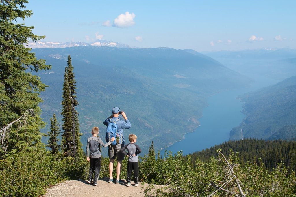 family hiking in mountains looking at view