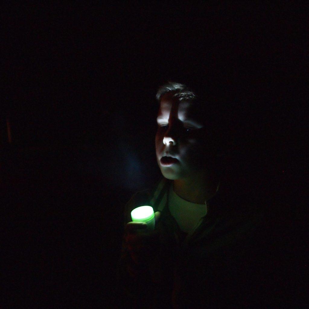 boy holding flashlight at night
