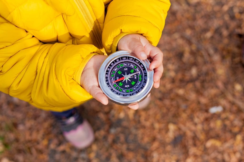 child on hike using compass