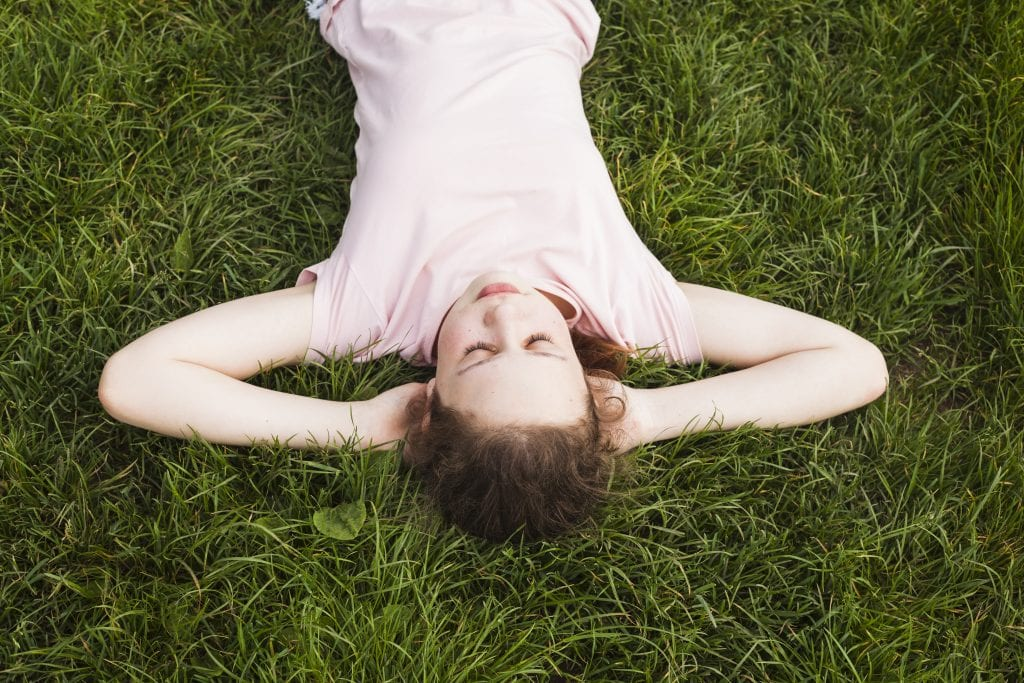 girl lying in grass, eyes closed