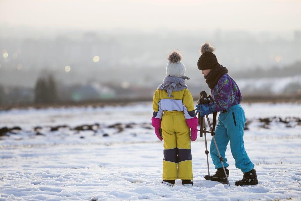 kids taking photos in snowy winter landscape