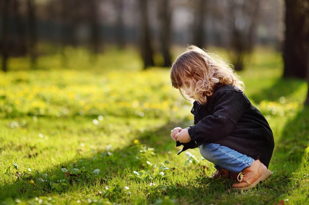 girl playing on grass in forest on sunny Spring day
