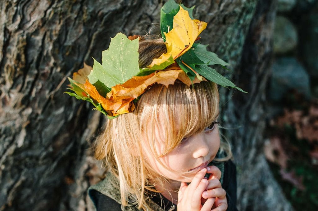 young girl wearing crown of autumn leaves